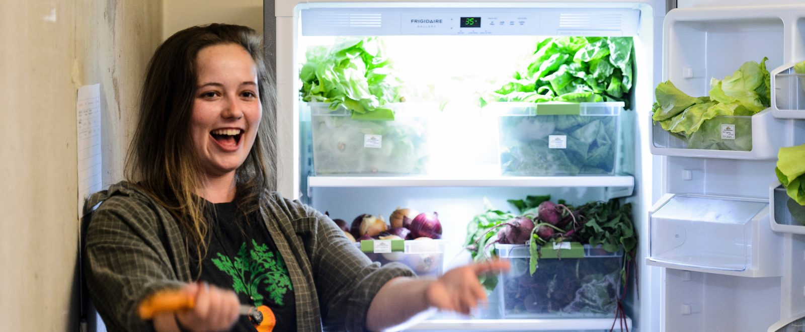 Hannah DePorter stands in front of the new refrigerator, door open displaying a bounty of fresh greens, onions, beets.