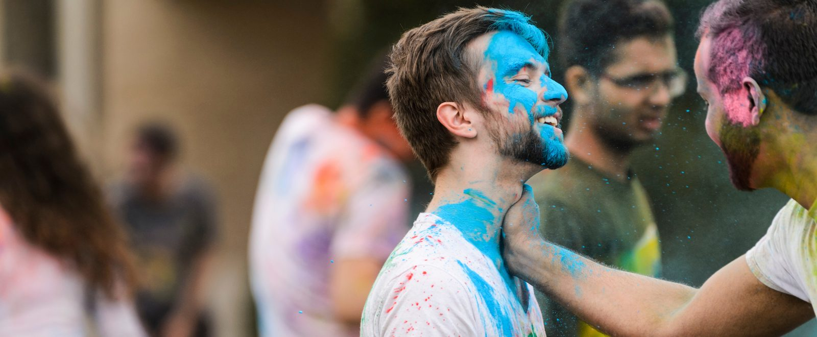 male student with blue chalked face smiles during the festival of colors, an Indian tradition.