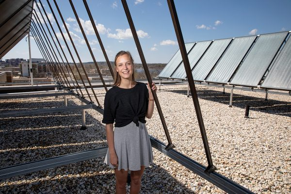 Leah Johnson poses for a portrait near the rooftop solar panels on Leopold Residence Hall at UW-Madison.