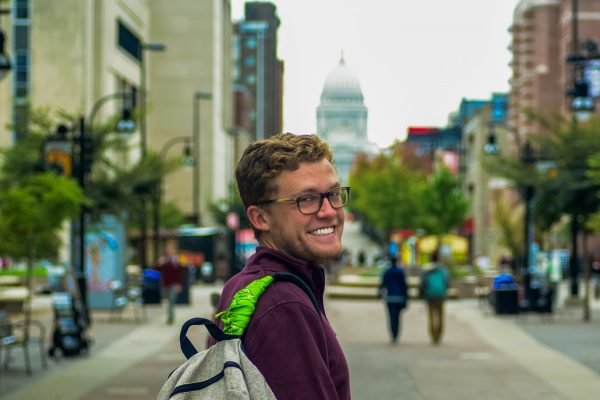 Student Colin Bass stands at the base of State Street, the capitol behind him in the distance, his backpack strap wrapped with a green bandana.