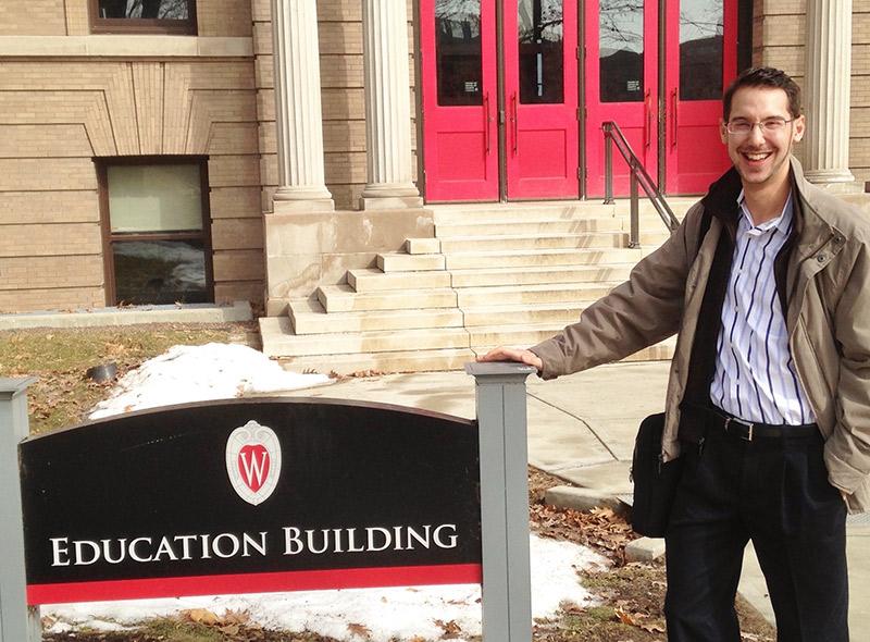 Brett Nachman standing next to the Education Building sign on Bascom Hill.